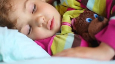 Little girl sleeping with toy bear in compartment of railway carriage — Stock Video