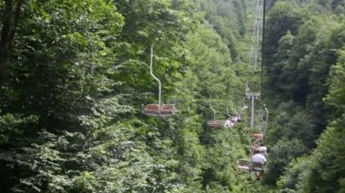 Tourists on moving funicular above mountain forest — Stock Video