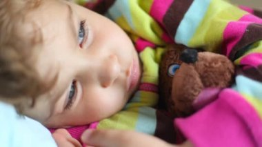 Cute sleepy little girl with toy bear lying in bed and blinking — Stock Video