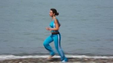 Young woman in tracksuit running on pebble coast, sea in background — Stock Video