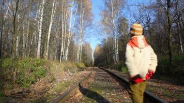 Boy walking along railroad tracks, from camera — Stock Video