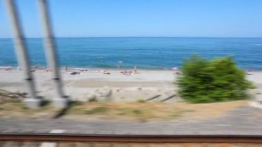 Sea beach with tourists, view from window of moving train — Stock Video