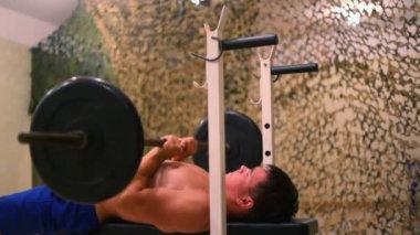 Jeune homme sportif en salle de gym faire presse pectorale sur banc de musculation — Vidéo
