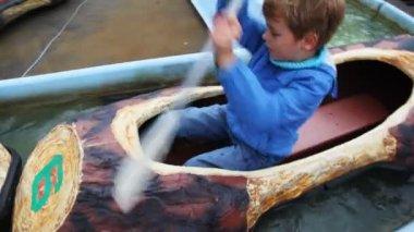 Chlapec a dívka řádek v malé lodě na vodě v parku přitažlivost — Stock video
