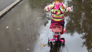 Little girl pedaling on wet asphalt with puddles, camera follow her — Stock Video