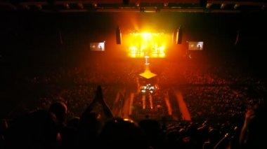 Zangers verschijnen op scène gevuld met gouden licht in concertzaal — Stockvideo