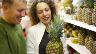 Smiling man and woman buying pineapple in supermarket — Stock Video