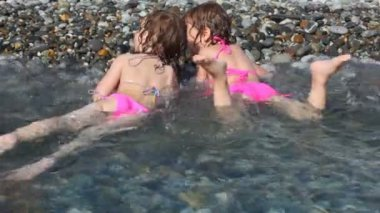 Two happy little girls lying on pebble beach with sea surf — Stock Video