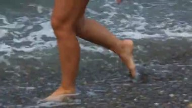 Feet with pedicure of woman walking on rocky beach with sea surf — Stock Video