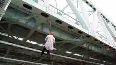 Man is chin up on cord suspended to iron bridge with help jumar — Stock Video