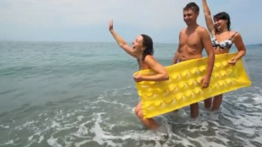 Two womans and man holds inflatable mattress stands on beach — Stock Video