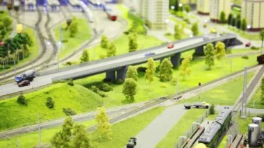 Toy train pushes empty cargo wagon on rail in modern toy city among roads, house and trees