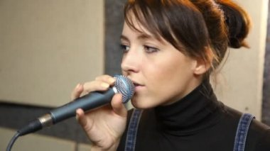 Young female vocalist with microphone singing in studio — Stock Video