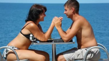 Man and woman in swimsuit sits at table, join hands, sea in background — Stock Video