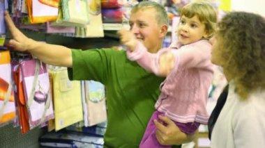 Familia con niña comprando ropa de cama en supermercado — Vídeo de Stock
