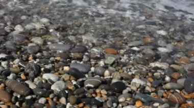 Sea surf with spume covering pebble coast, macro shooting — Stock Video