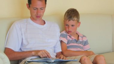 Father with little son sits on divan reads children's book — Stock Video