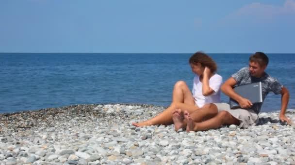 Mujer que se sienta y el hombre con el cuaderno levantarse en playa rocosa — Vídeo de stock