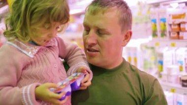 Homme avec la petite fille, acheter des yaourts au supermarché — Vidéo