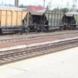 Two working woman go on railway station againts freight train with pebble - Stockfoto