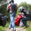 Two sits on grass, then sit down on motorcycles and leave - Stockfoto