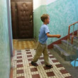 Boy stop in tracks on stair platform in apartment house. Moving camera — Stock Video
