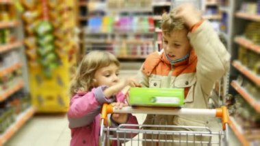 Boy and little girl with shopping trolley looks at goods box in supermarket — Stock Video