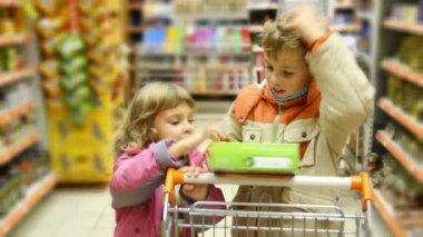 Esya kutusu süpermarkette alışveriş arabası ile küçük kız ve erkek görünüyor — Stok video