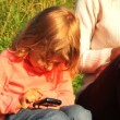 Daughter and mother sits green lawn and play in communicator — Stock Video
