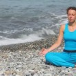 Young woman in tracksuit sits in pose of lotus on pebble beach against sea — Stockvideo