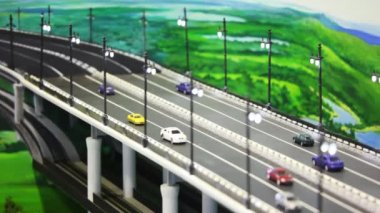 Toy tiny automobile cars stand on bridge before drawn panorama. image is washed away — Stock Video