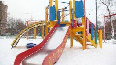 Niña jugando en la diapositiva en el patio de la ciudad de nieve, invierno — Vídeo de stock
