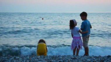 Kids throwing pebbles to sea, standing in pebble beach — Stock Video