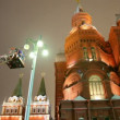 Mounter changing workless street lamp on moscow night street - Stock Photo