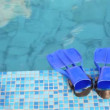 Blue flippers is on mosaic edge of swimming pool with clear water - Stock Photo