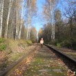 Boy running along railroad tracks, to camera — Stock Video