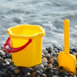 Royalty-Free Stock Vector Image: Yellow children\'s bucket with scoop on stone seacoast