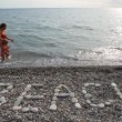 Woman with little girl running on sea surf, BEACH inscription in foreground — Stock Video