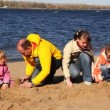 Family of mother, father, son and daughter build hills of sand on river beach — Stock Video