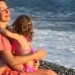 Young mother with her little daughter embracing in pebble beach near sea — Stock Video