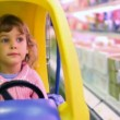 Royalty-Free Stock Vector Image: Little girl sitting in car-shopping trolley in supermarket