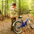 Boy get on bicycle and riding in autumn forest with leaves — Stock Video