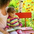 Mother and daughter reading book on the bench in the yard — Vídeo Stock