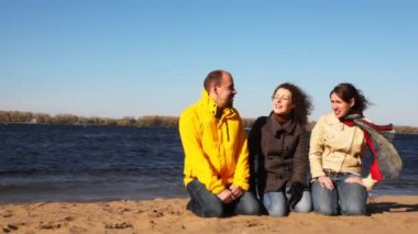 Man and two woman sits on sand of river and talk with each other — Stock Video