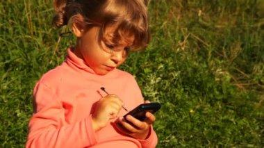 Dziewczyna w parku, przytrzymaj ppc w ręce i dotknąć go z stylos latem — Wideo stockowe