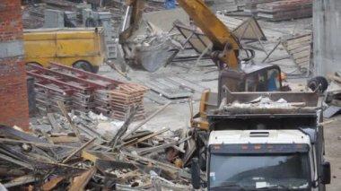Draga carrega a poeira do edifício em caminhão no canteiro de obras — Vídeo Stock
