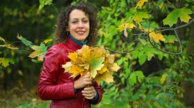 Young woman with maple leaves in hands standing in autumn park — Stock Video