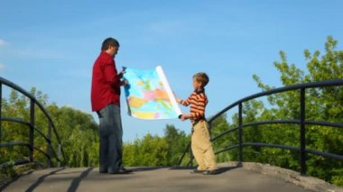 Man with boy unrolling map of europe — Stock Video