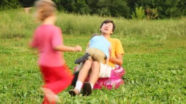 Man, boy and girl sit in children's inflatable armchair on field in park and play the fool — Vídeo Stock