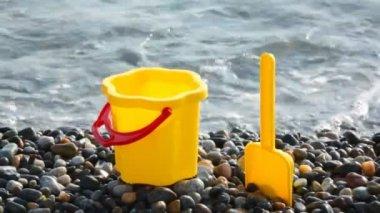 Yellow children's bucket with scoop on stone seacoast — Vídeo de Stock